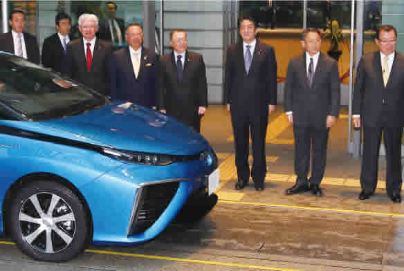 Prime Minister Shinzo Abe (third from right), Hiroya Kawasaki (front left) and others stand beside the Toyota Mirai