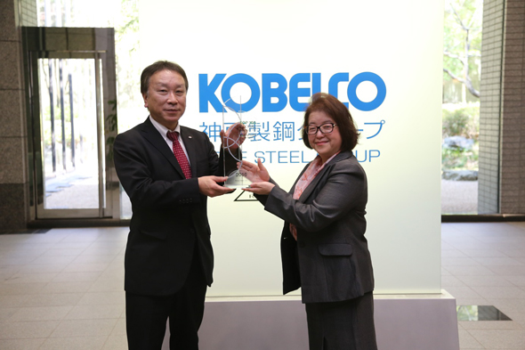 Yoshiko Tanahashi, Vice President, Strategic Accounts and Partners, Clarivate Analytics (right) presents the trophy to Kobe Steel's Toshiya Miyake, Director, Managing Executive Officer, who oversees research and development at the company.